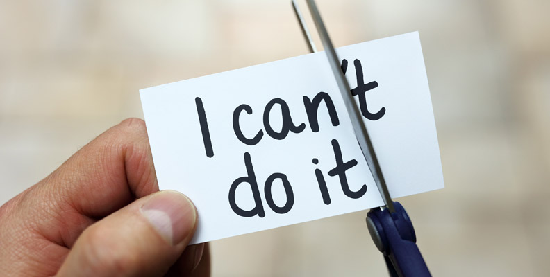 hand holding card that says I can't do it, scissors cutting off the 't, leaving I can do it