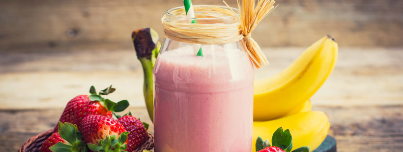 whole fruit smoothie in a jar with bananas and strawberries next to it
