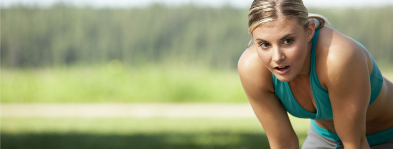 Woman bending over to breathe after working out hard.