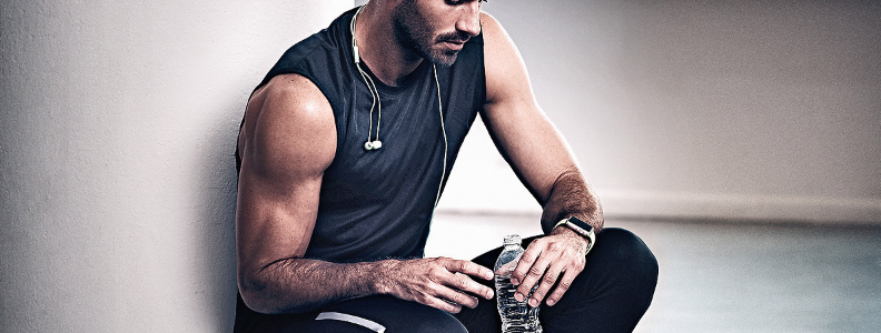 Man drinking water during a break from working out.