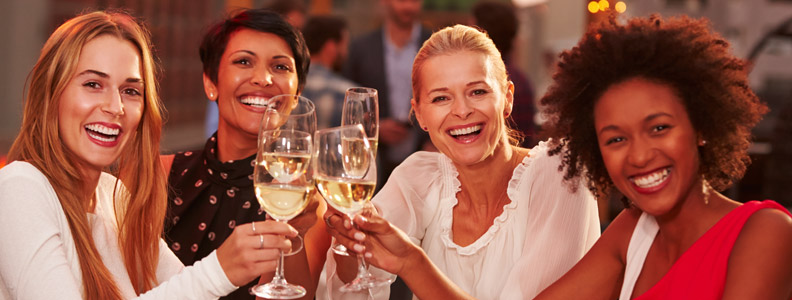 4 ladies toasting with a glass of white wine