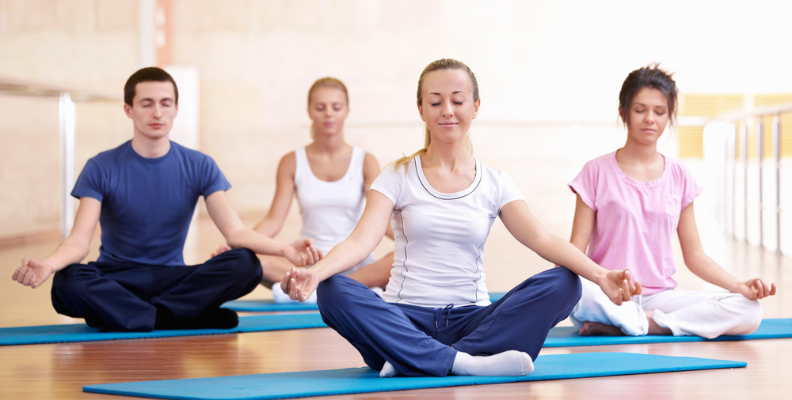 A group sitting on yoga mats, meditating. Meditation helps with memory loss.