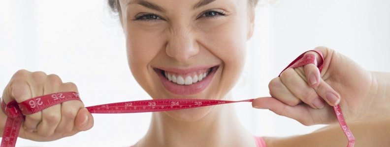 Young woman smiling and holding a measuring tape in front of her