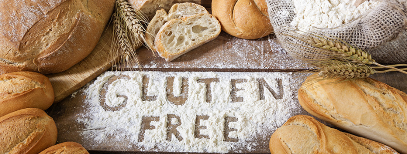 """breads around flour spread on a table with """"Gluten free"""" written in the flour"""