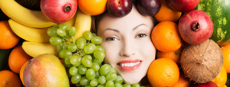 woman's face surrounded by whole fruits