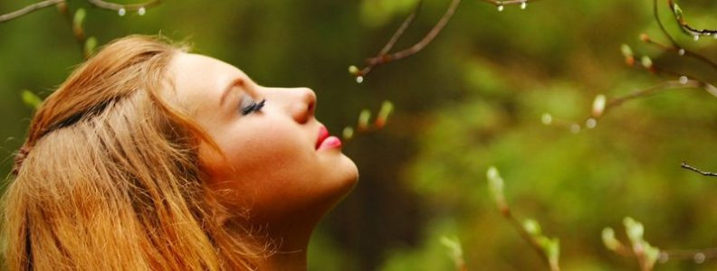 serene young woman outdoors, looking up at the sky with eyes closed