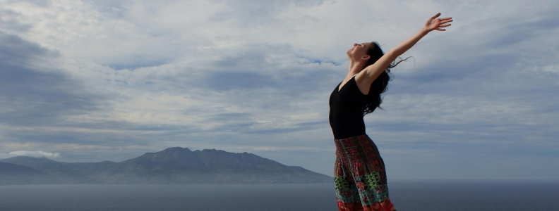 Freedom: woman on a mountain top with arms held high and wide, looking up at the sky