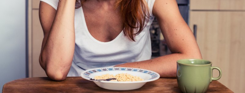 woman looking depressed with a bowl of cereal and cup of coffee in front of her.