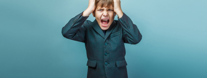 Boy screaming and holding his head. Long-term anxiety can be a cause for migraine headaches.