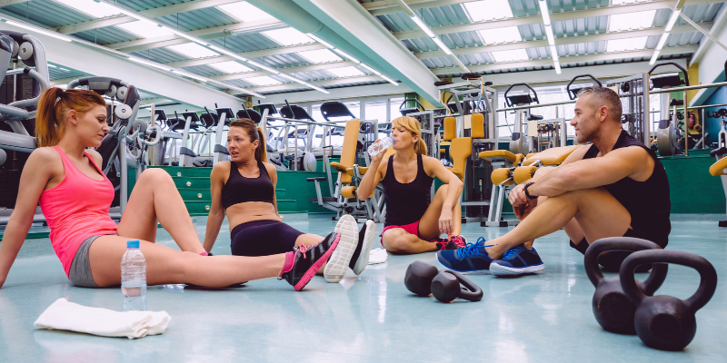 Group sitting on the gym floor. Exercise is great for the brain and helps prevent memory loss.