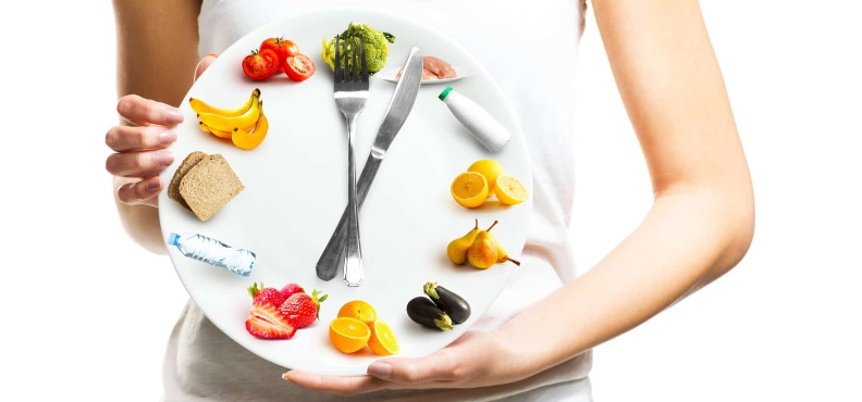images of foods on a plate in clock configuration with fork and knife as clock hands.