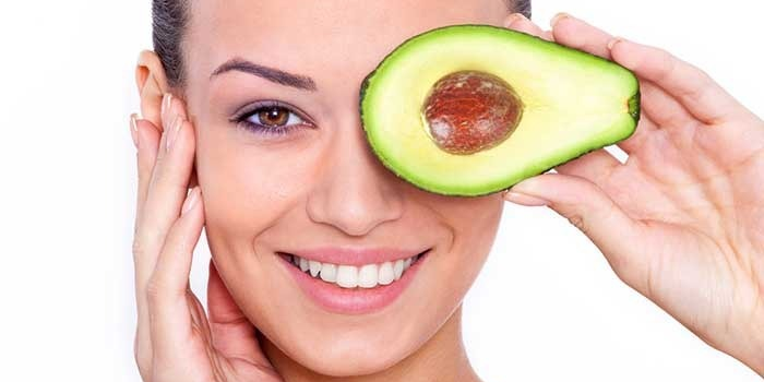 A woman holding half an avocado up to her eye
