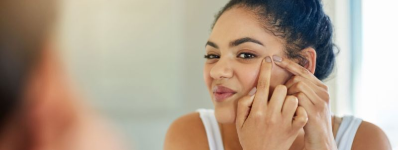 young woman looking in a mirror and popping a blackhead with her fingernails