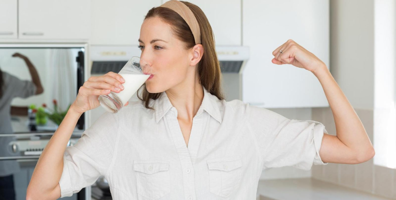 woman drinking milk and flexing bicep