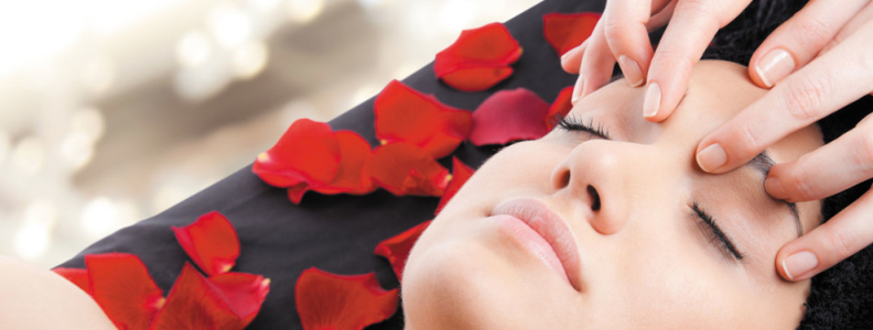 image of a woman laying down getting massage during a facial with rose petals around her head