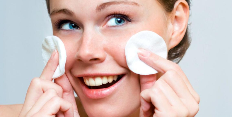 woman putting tonic on her face with cotton pads