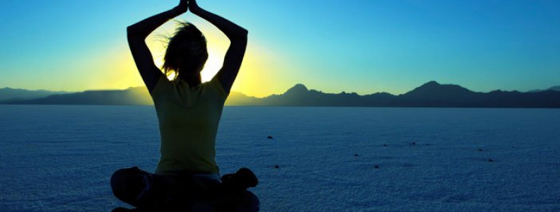 woman practicing meditation and mindfulness outside at dawn