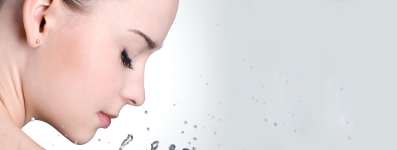 image of a woman with long eyelashes and flawless skin looking down and water droplets splashing