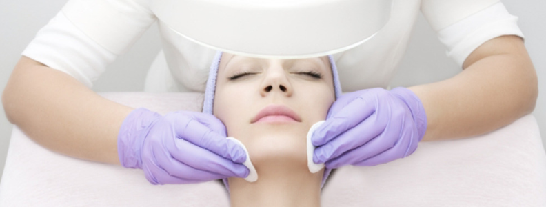 image of a woman getting a facial with lilac towel on her head and aesthetician with lilac gloves applying treatment with cotton pads