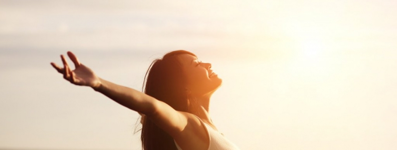woman smiling with her face up toward the sun