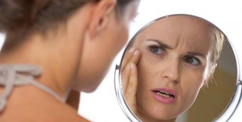 woman looking into a mirror at her face and frowning