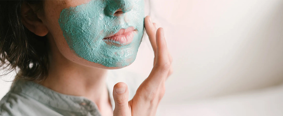 Woman putting on a creamy facial mask.