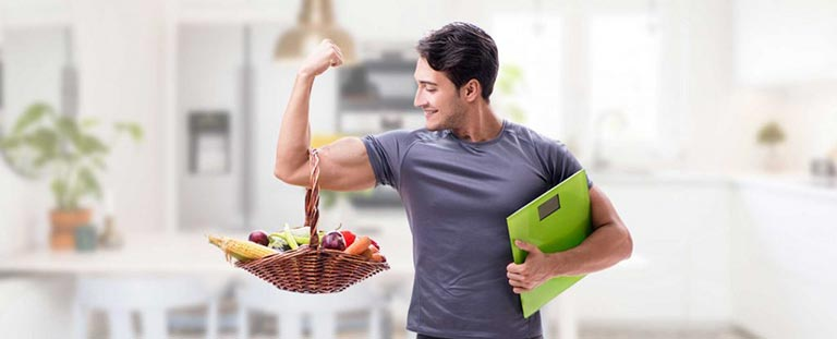 man flexing his bicep with a basket of fruit and vegetables hanging from his arm.