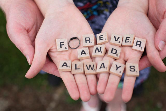 Man and woman hands holding Scrabble tiles arranged to say Forever and Always.